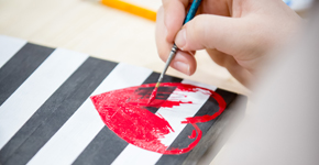Heart being painted on a black and white striped canvas