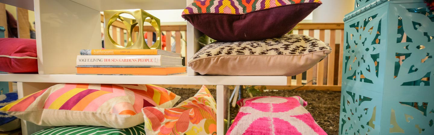 Colorful cushions on shelves with a few books